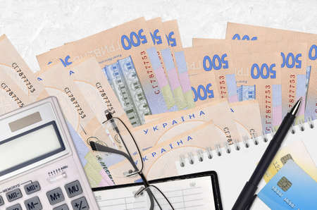 500 Ukrainian hryvnias bills and calculator with glasses and pen. Tax payment season concept or investment solutions. Financial planning or accountant paperwork Фото со стока