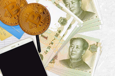 1 Chinese yuan bills and golden bitcoins with smartphone and credit cards. Cryptocurrency investment concept. Crypto mining or trading transactions