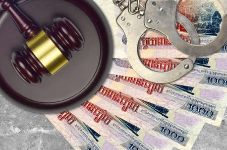 1000 Cambodian riels bills and judge hammer with police handcuffs on court desk. Concept of judicial trial or bribery. Tax avoidance or tax evasion