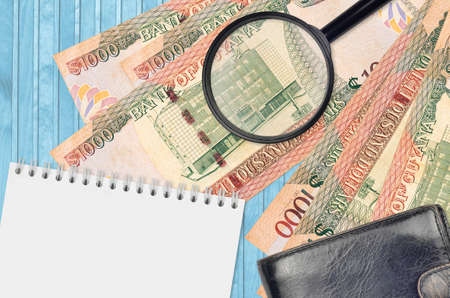 1000 Guyanese dollars bills and magnifying glass with black purse and notepad. Concept of counterfeit money. Search for differences in details on money bills to detect fake money Stok Fotoğraf