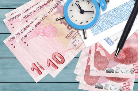 10 Turkish liras bills and alarm clock with pen and envelopes. Tax season concept, payment deadline for credit or loan. Financial operations using postal service. Quick money transfer