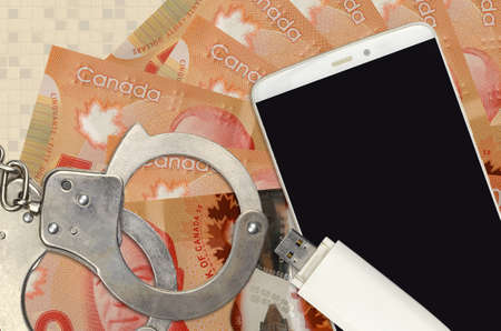 50 Canadian dollars bills and smartphone with police handcuffs. Concept of hackers phishing attacks, illegal scam or online spyware soft distribution
