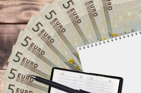 5 euro bills fan and notepad with contact book and black pen. Concept of financial planning and business strategy. Accounting and investment