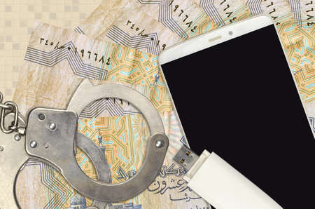 25 Egyptian piastres bills and smartphone with police handcuffs. Concept of hackers phishing attacks, illegal scam or online spyware soft distribution