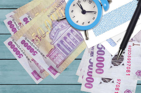 50,000 Romanian leu bills and alarm clock with pen and envelopes. Tax season concept, payment deadline for credit or loan. Financial operations using postal service. Quick money transfer