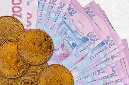 200 Ukrainian hryvnias bills and golden bitcoins. Cryptocurrency investment concept. Crypto mining or trading transactions