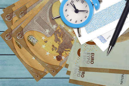 50 euro bills and alarm clock with pen and envelopes. Tax season concept, payment deadline for credit or loan. Financial operations using postal service. Quick money transfer
