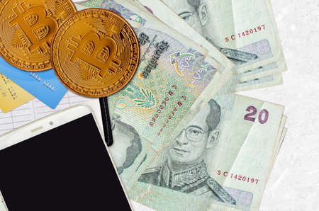 20 Thai Baht bills and golden bitcoins with smartphone and credit cards. Cryptocurrency investment concept. Crypto mining or trading transactions