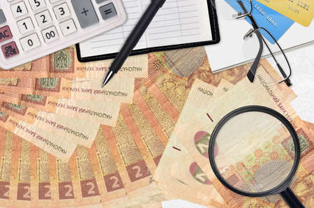 2 Ukrainian hryvnias bills and calculator with glasses and pen. Tax payment season concept or investment solutions. Searching a job with high salary earnings