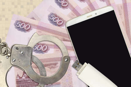 500 russian rubles bills and smartphone with police handcuffs. Concept of hackers phishing attacks, illegal scam or online spyware soft distribution Zdjęcie Seryjne