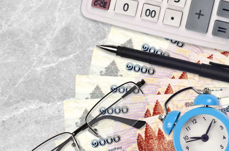 1000 Cambodian riels bills and calculator with glasses and pen. Business loan or tax payment season concept. Financial planning and time to pay taxes