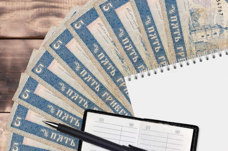 5 Ukrainian hryvnias bills fan and notepad with contact book and black pen. Concept of financial planning and business strategy. Accounting and investment
