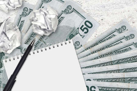 50 US dollars bills and balls of crumpled paper with notepad. Bad ideas or less of inspiration concept. Searching ideas for investment