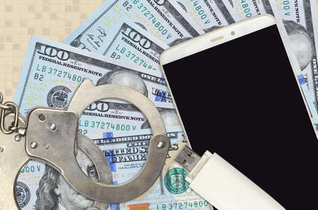 100 US dollars bills and smartphone with police handcuffs. Concept of hackers phishing attacks, illegal scam or online spyware soft distribution Zdjęcie Seryjne
