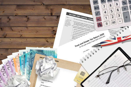English Tax form sa900 Trust and estate tax return 2020 from HM revenue and customs lies on table with office items. HMRC paperwork and tax paying process in United Kingdom of Great Britain