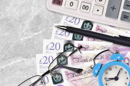 20 British pounds bills and calculator with glasses and pen. Business loan or tax payment season concept. Financial planning and time to pay taxes Stock fotó