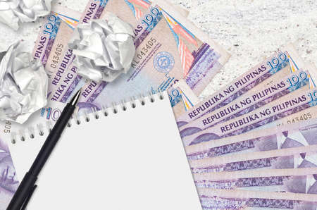 100 Philippine piso bills and balls of crumpled paper with notepad. Bad ideas or less of inspiration concept. Searching ideas for investment