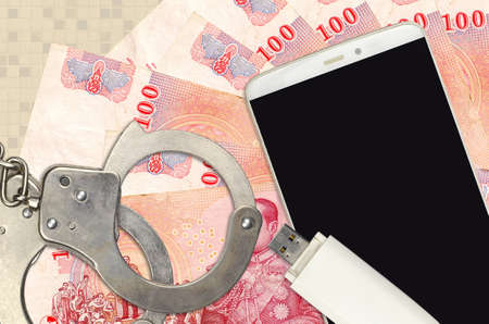100 Thai Baht bills and smartphone with police handcuffs. Concept of hackers phishing attacks, illegal scam or online spyware soft distribution