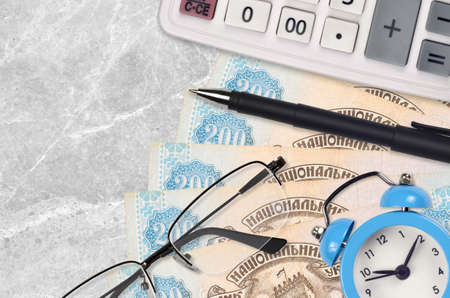 200 Ukrainian hryvnias bills and calculator with glasses and pen. Business loan or tax payment season concept. Financial planning and time to pay taxes