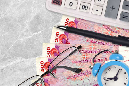 500 Cambodian riels bills and calculator with glasses and pen. Business loan or tax payment season concept. Financial planning and time to pay taxes Stock fotó
