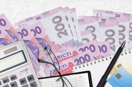 200 Ukrainian hryvnias bills and calculator with glasses and pen. Tax payment season concept or investment solutions. Financial planning or accountant paperwork Фото со стока