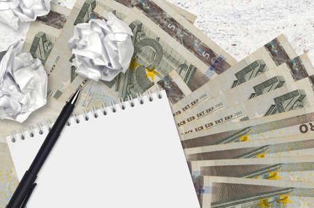5 euro bills and balls of crumpled paper with notepad. Bad ideas or less of inspiration concept. Searching ideas for investment