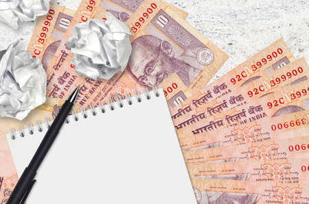 10 Indian rupees bills and balls of crumpled paper with notepad. Bad ideas or less of inspiration concept. Searching ideas for investment Stock fotó