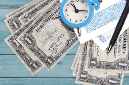 1 US dollar bills and alarm clock with pen and envelopes. Tax season concept, payment deadline for credit or loan. Financial operations using postal service. Quick money transfer