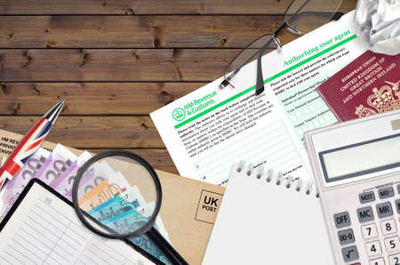 English form 64-8 Authorizing your agent from HM revenue and customs lies on table with office items. HMRC paperwork and tax paying process in United Kingdom of Great Britain