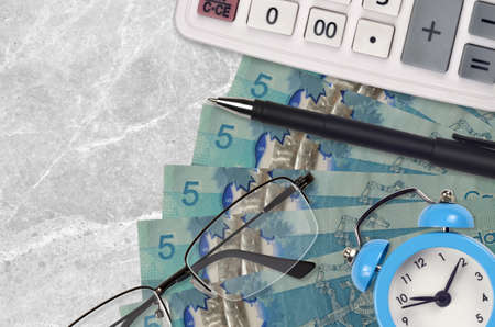 5 Canadian dollars bills and calculator with glasses and pen. Business loan or tax payment season concept. Financial planning and time to pay taxes Stock fotó