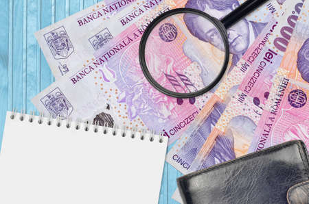 50,000 Romanian leu bills and magnifying glass with black purse and notepad. Concept of counterfeit money. Search for differences in details on money bills to detect fake money