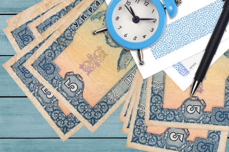 5 Ukrainian hryvnias bills and alarm clock with pen and envelopes. Tax season concept, payment deadline for credit or loan. Financial operations using postal service. Quick money transfer Stock fotó