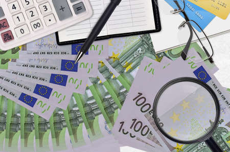 100 Euro bills and calculator with glasses and pen. Tax payment season concept or investment solutions. Searching a job with high salary earnings
