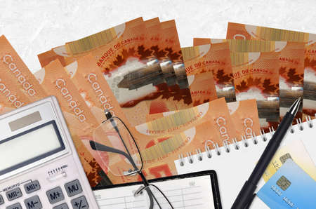 50 Canadian dollars bills and calculator with glasses and pen. Tax payment season concept or investment solutions. Financial planning or accountant paperwork