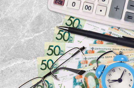 50 Belorussian rubles bills and calculator with glasses and pen. Business loan or tax payment season concept. Financial planning and time to pay taxes