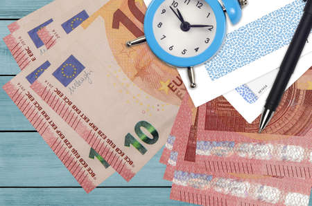 10 euro bills and alarm clock with pen and envelopes. Tax season concept, payment deadline for credit or loan. Financial operations using postal service. Quick money transfer