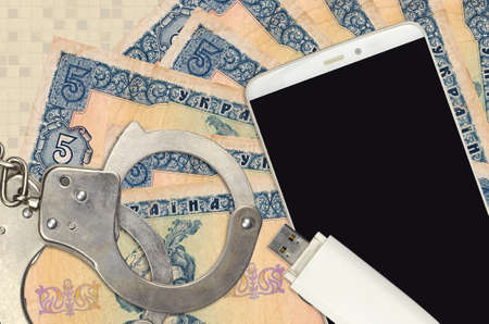 5 Ukrainian hryvnias bills and smartphone with police handcuffs. Concept of hackers phishing attacks, illegal scam or online spyware soft distribution Zdjęcie Seryjne