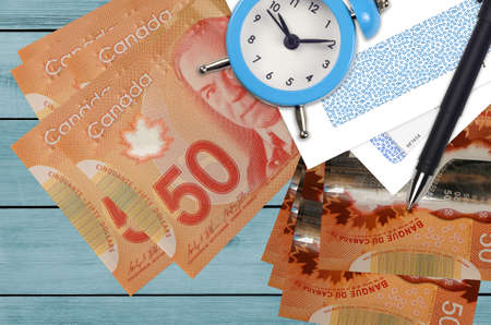 50 Canadian dollars bills and alarm clock with pen and envelopes. Tax season concept, payment deadline for credit or loan. Financial operations using postal service. Quick money transfer