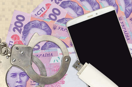 200 Ukrainian hryvnias bills and smartphone with police handcuffs. Concept of hackers phishing attacks, illegal scam or online spyware soft distribution