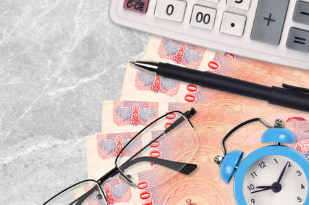 100 Thai Baht bills and calculator with glasses and pen. Business loan or tax payment season concept. Financial planning and time to pay taxes