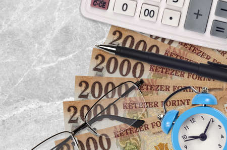 2000 Hungarian forint bills and calculator with glasses and pen. Business loan or tax payment season concept. Financial planning and time to pay taxes Stock fotó