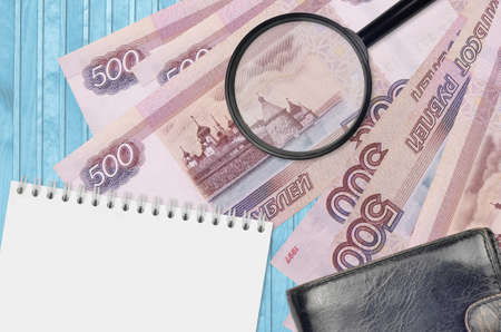 500 russian rubles bills and magnifying glass with black purse and notepad. Concept of counterfeit money. Search for differences in details on money bills to detect fake money