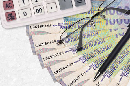 1000 Indonesian rupiah bills fan and calculator with glasses and pen. Business loan or tax payment season concept. Financial planning