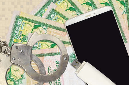 10 Sri Lankan rupees bills and smartphone with police handcuffs. Concept of hackers phishing attacks, illegal scam or online spyware soft distribution Zdjęcie Seryjne