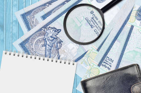 50 Sri Lankan rupees bills and magnifying glass with black purse and notepad. Concept of counterfeit money. Search for differences in details on money bills to detect fake money Фото со стока