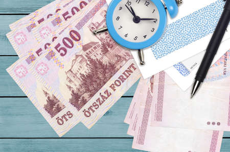 500 Hungarian forint bills and alarm clock with pen and envelopes. Tax season concept, payment deadline for credit or loan. Financial operations using postal service. Quick money transfer