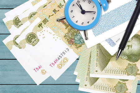 1 Chinese yuan bills and alarm clock with pen and envelopes. Tax season concept, payment deadline for credit or loan. Financial operations using postal service. Quick money transfer