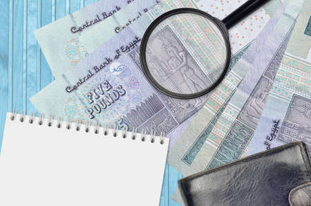 5 Egyptian pounds bills and magnifying glass with black purse and notepad. Concept of counterfeit money. Search for differences in details on money bills to detect fake money