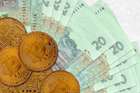 20 Ukrainian hryvnias bills and golden bitcoins. Cryptocurrency investment concept. Crypto mining or trading transactions Imagens