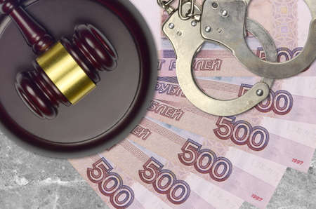 500 russian rubles bills and judge hammer with police handcuffs on court desk. Concept of judicial trial or bribery. Tax avoidance or tax evasion